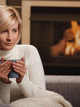 Frau mit Kaffee vor Kamin